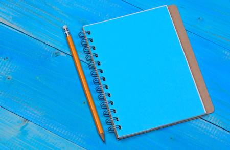 sheet of paper: Empty notebook with pencil on blue wooden table