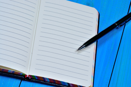 sheet of paper: Empty notebook with pen on blue table close-up