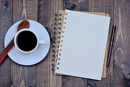 Notebook with coffee cup on wooden table Stock Photo