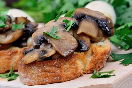 desk: Bruschetta with mushroom on chopping board close-up