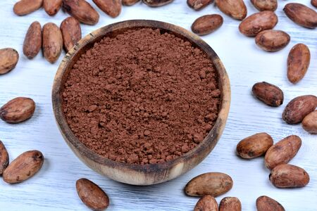 Cacao powder in a bowl with beans on white wooden table Banco de Imagens