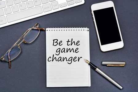 Be the game changer. Text on notebook on a black background Stock Photo