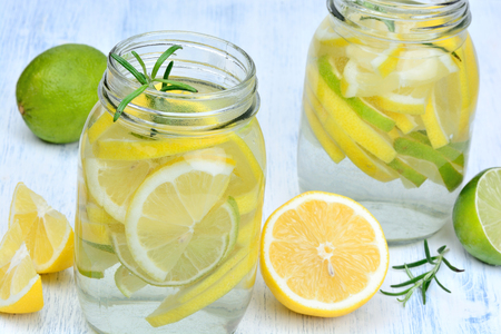 Water with fresh citrus and rosemary in a jars on table