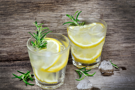 Fresh lemon with water in a glasses on old wood table