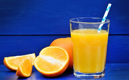Glass with orange juice on blue wooden table