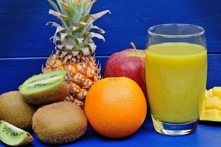 Fresh glass of juice with fruit mix on table