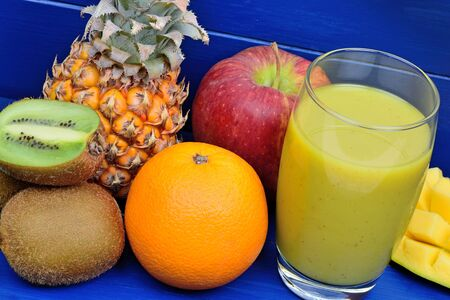 Fresh glass of juice with fruit mix on a wood table close up