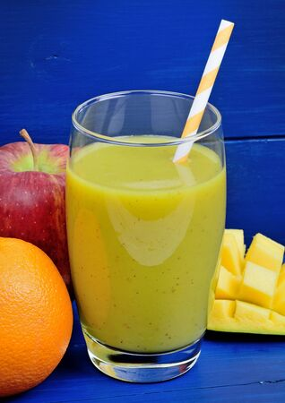 Mix of fresh fruits smoothie in a glass on a wood table