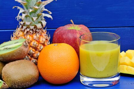 Delicious smoothie in a glass on a blue wood table