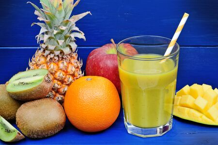 Fresh glass of juice with fruits on blue wooden table