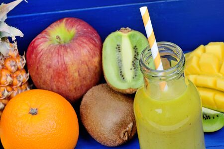 Glass of juice with fruit mix on blue wooden table