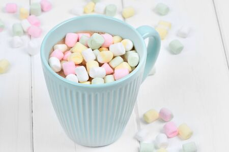 Hot chocolate with colorful marshmallows in a cup on a white wood table