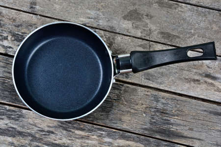 Empty iron pan on a wood table