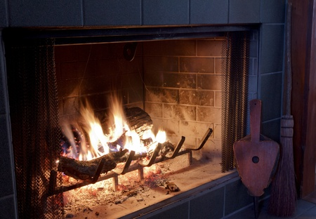 Fire in a fireplace with bellows and broom photo