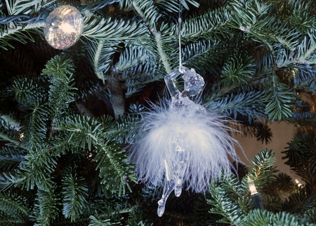 Ballerina ornament on a Christmas tree with lights. The ballerina is wearing a feather tutu. Closeup photo