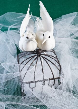 Lovebirds perched on a cage with tulle and green textile with wedding bands inside the cage 版權商用圖片
