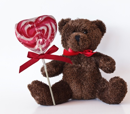 Brown teddy bear with lollipop and red ribbon isolated on a white background Stock Photo - 13795005