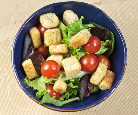 arugola: Summer Salad with summer greens, tomatos, croutons in a blue bowl with yellow cloth. Overhead view. Stock Photo