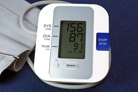 cuff: Bood Pressure Monitor with cuff and showing hypertension. Stock Photo