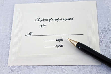 An accept or regret card for a wedding or party  This card is engraved and on ivory colored paper on a white background  A black and gold pen is ready for to respond  Stock Photo