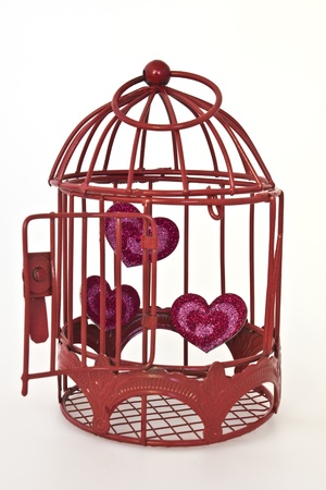 Red glitter hearts in a red cage with the door open to set the hearts free and isolated on a white background. photo