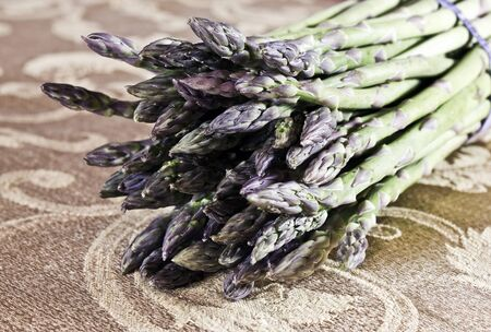 gold table cloth: Asparagus in a bunch taken from a side view and closeup on a gold table cloth
