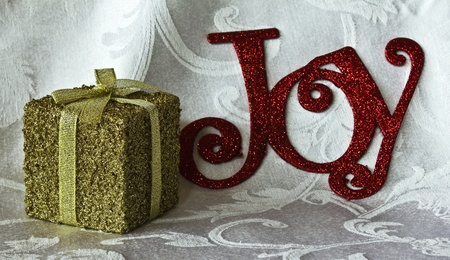 Gold package with bow and ribbon on a white brocade background. The word Joy in the background.  photo