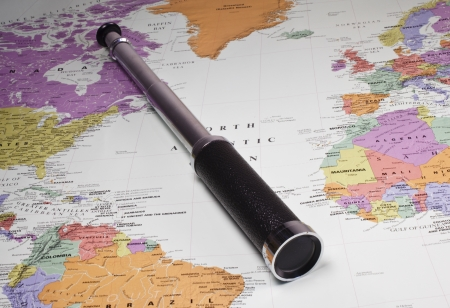 Monocular spy glass on a map of the world photo