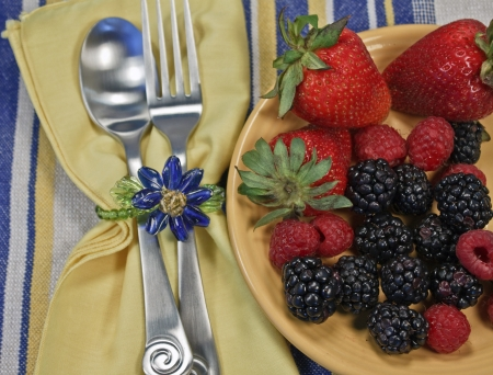 napkin ring: Assorted berries on a yellow plate on a striped textile with napkin, silverware, and napkin ring. Stock Photo