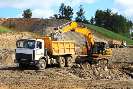 dumper truck: Excavator loading truck shot against the background of the pit and blue sky Stock Photo