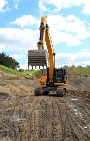 eddy: excavator photographed against the background of excavation and blue sky
