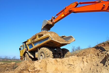 Excavator loading truck shot against the background of the pit and blue sky photo