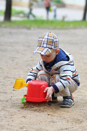 little boy playing in the sandbox photo