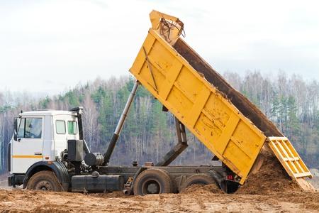 camion volteo: Vuelca cami�n de descarga de una monta�a de tierra desde el cuerpo Foto de archivo