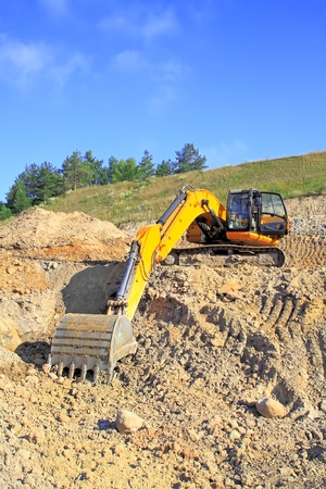 truckload: Excavator loading truck shot against the background of the pit and blue sky Stock Photo