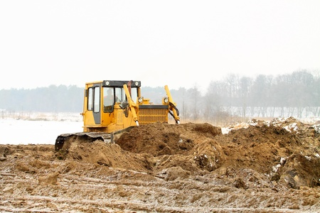 bulldozer loader at winter frozen soil excavation works photo