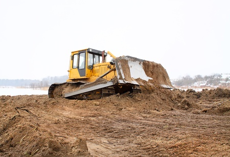 bulldozer loader at winter frozen soil excavation works photo