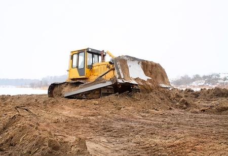 bulldozer loader at winter frozen soil excavation works