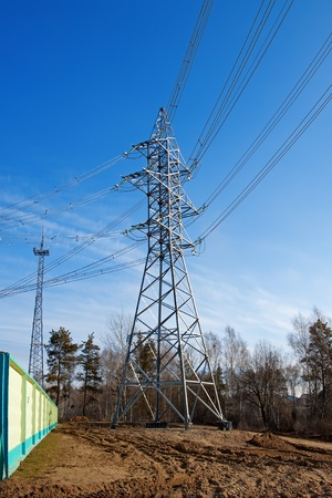 The high-voltage support standing on the earth, against the blue sky photo