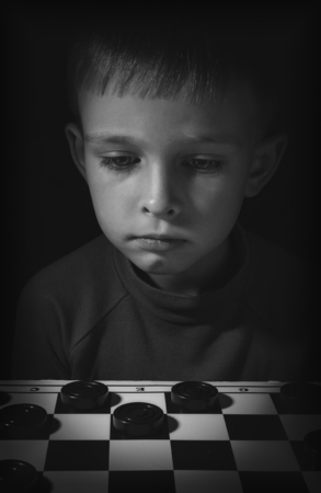 smart kid: The boy is thinking over the course of playing checkers is photographed in low key