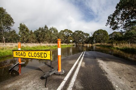 Road closed due to flooding showing Road closed sign