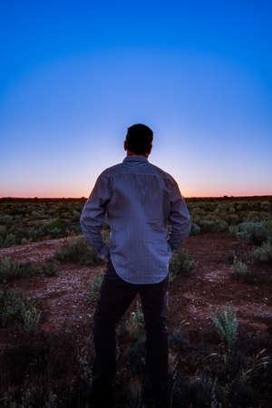 Man surveying his land at sunset