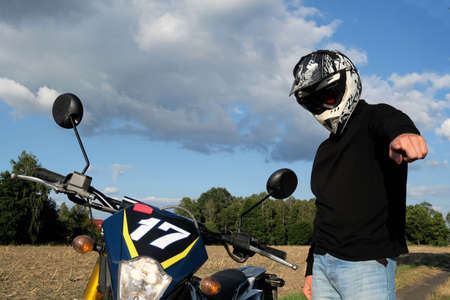 man with a motocycle in a helmet pointing finger on a country road