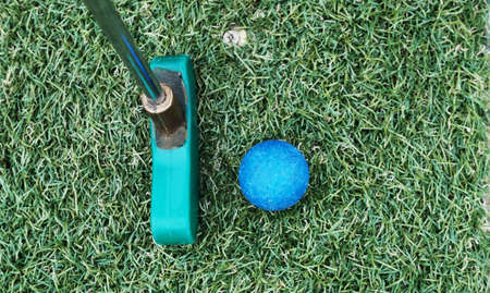 club and ball on green artificial grass on mini golf course.