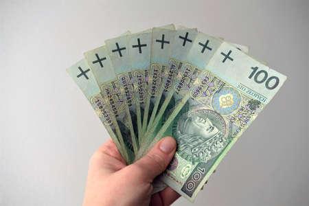 range of one hundred polish zloty notes held in hand.