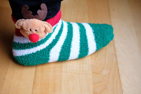 girls foot wearing funny stripey christmas sock with reindeer ornament