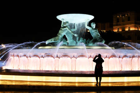 young woman taking a photo of illuminated fountain with three tritons - landmark of Valetta, Malta. Night shot Archivio Fotografico