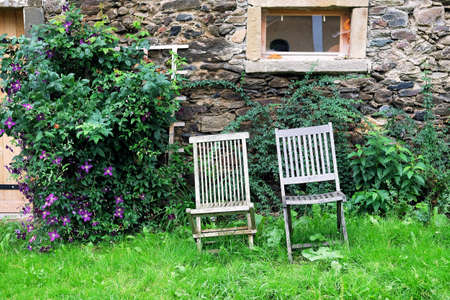 Two weathered woden chairs standing in an overgrown garden outside a rustic old stone barn Standard-Bild