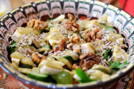 Big bowl of salad with walnuts, grapes, and sunflower seeds rich in healthy Omega-3 and Omega-6 fats and fiber