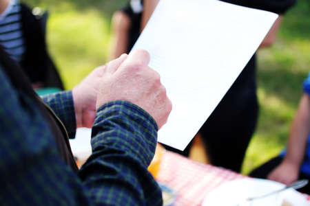 senior man's hand holding a sheet of paper with an anniversary speech, which he makes at his sister's birthdady party Standard-Bild